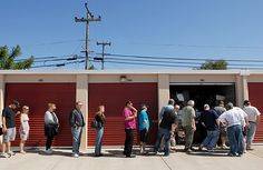Potential bidders wait in line to get a quick glimpse of a storage unit on the auction block before bidding on it during a storage locker auction at the Solano Storage Center in Fairfield Friday morning.